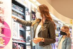 Frau mit Maske an Kosmetikregal im Drogeriemarkt mit Mädchen mit Maske im Hintergrund