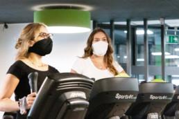 Zwei Frauen mit Masken auf Fitnessgeräten im Sportstudio
