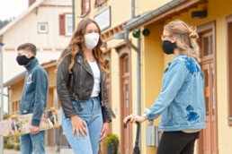 zwei Mädchen mit Masken stehen an einem Bahnhof mit einem Jungen mit Maske und Skateboard im Hintergrund