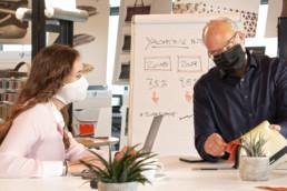 Frau und Mann mit Maske sitzen am Tisch in Büro mit Papier und Statistiken