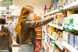 Frau mit Maske im Supermarkt am Regal, im Hintergrund befinden sich ein Mann und Kind mit Maske