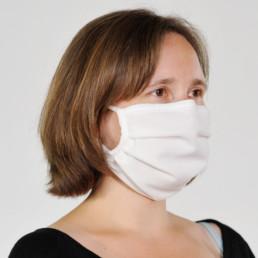 Frau mit weißer Mund-Nasen-Maske mit elastischem Gummiband von seitlich-vorne