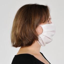 Frau mit weißer Mund-Nasen-Maske mit elastischem Gummiband von rechts