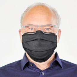 Mann mit schwarzer Mund-Nasen-Maske mit elastischem Gummiband von vorne