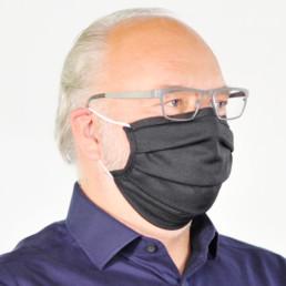 Mann mit schwarzer Mund-Nasen-Maske mit elastischem Gummiband von seitlich-vorne
