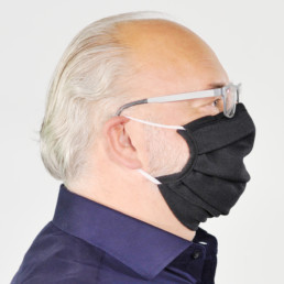 Mann mit schwarzer Mund-Nasen-Maske mit elastischem Gummiband von rechts