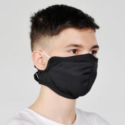Junge mit schwarzer Mund-Nasen-Maske mit Klettverschluss von seitlich-vorne