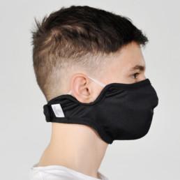 Junge mit schwarzer Mund-Nasen-Maske mit Klettverschluss von rechts