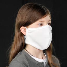 Kind mit weißer Mund-Nasen-Maske mit Klettverschluss von seitlich-vorne
