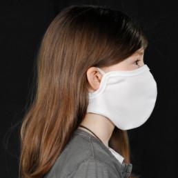Kind mit weißer Mund-Nasen-Maske mit Klettverschluss von rechts