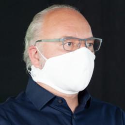 Mann mit weißer Mund-Nasen-Maske mit Klettverschluss von seitlich-vorne
