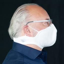 Mann mit weißer Mund-Nasen-Maske mit Klettverschluss von rechts
