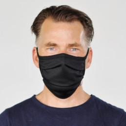 Mann mit schwarzer Mund-Nasen-Maske mit Schnürung von vorne