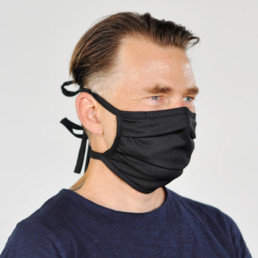 Mann mit schwarzer Mund-Nasen-Maske mit Schnürung von seitlich-vorne