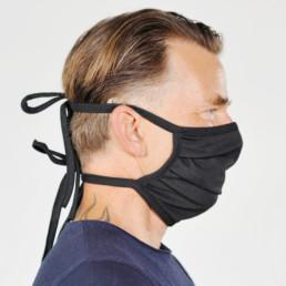 Mann mit schwarzer Mund-Nasen-Maske mit Schnürung von rechts