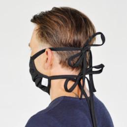 Mann mit schwarzer Mund-Nasen-Maske mit Schnürung von seitlich-hinten